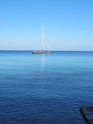 a boat moored off shore, blue on blue on blue